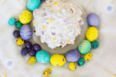 Yellow and violet Easter eggs with had drawings of butterflies,. Easter cake with white glaze oj round plate surrounded with colorful  Easter eggs with had Stock Images