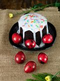 Easter cake with white glazing and sprinkle and red coloured eggs. On sackcloth Stock Images
