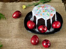 Easter cake with white glazing and sprinkle and red coloured eggs. On sackcloth Stock Image