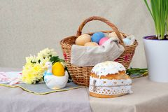 Easter cake and the bascket with colored eggs and yellow flowers, on the table royalty free stock photo
