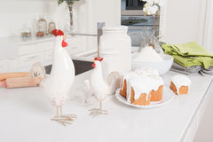 Easter cakes and cock are on kitchen. Cakes, flour and cock service are in the kitchen with white furniture in Easter eve Royalty Free Stock Photography