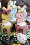Easter cakes and gingerbread rabbits on wooden background. View Royalty Free Stock Photo