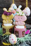 Easter cakes and gingerbread rabbits on wooden background. View Stock Image