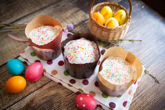 Easter cakes Kulich. With icing and sprinkles, on wood background, with vibrant easter eggs Royalty Free Stock Photos