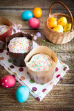 Easter cakes Kulich. With icing and sprinkles, on wood background, with vibrant easter eggs Royalty Free Stock Images