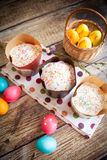 Easter cakes Kulich. With icing and sprinkles, on wood background, with vibrant easter eggs Royalty Free Stock Image