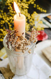 Easter candle. In a glass against a background yellow flowers Royalty Free Stock Photos