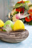 Easter candles in ceramic bowl decorated with quail feathers Royalty Free Stock Photos