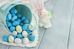 Easter Candy Eggs. A blue tin bucket tipped over, spilling Easter candy eggs onto a table. Shallow depth of field Royalty Free Stock Images