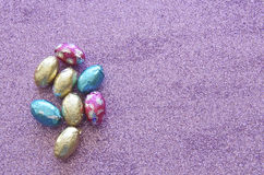 Easter Candy. A selection of colourful, foil wrapped chocolate Easter eggs on a sparkly purple background Stock Photo