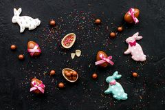 Easter candy. Traditional Easter signs and symbols. Chocolate Easter eggs and Easter bunny cookies. Black background top. View Stock Images