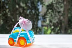 Easter blue car with a white egg. Easter car blue color with white egg tied with pink ribbon rides on the table against the background of greenery royalty free stock photos