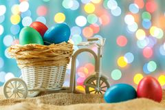 Easter card, colored eggs in the nest. Toy Bicycle with a cart. Royalty Free Stock Photo