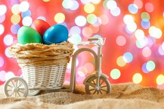 Easter card, colored eggs in the nest. Toy Bicycle with a cart. Royalty Free Stock Photography
