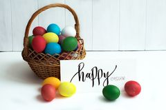 Easter card with colorful Easter eggs in a basket and calligraphic inscription `Happy Easter` royalty free stock photography