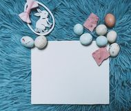 Easter card with copy space for your text. A blank card, eggs and a bunny. Blue background. stock image