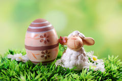 Easter card with cute lamb and egg on the grass Stock Images