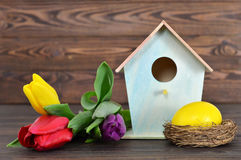 Easter card with Easter egg in the nest, birdhouse and spring flowers Royalty Free Stock Photography