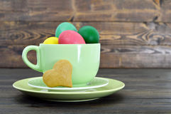Easter card with Easter eggs in the cup and heart shaped cookie Royalty Free Stock Photo