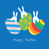 Easter card with funny bunnies and eggs. Easter card with a funny little bunnies and large Easter eggs on blue background Royalty Free Stock Image