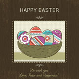 Easter card with nest full of colored eggs on wooden background. Stock Photo