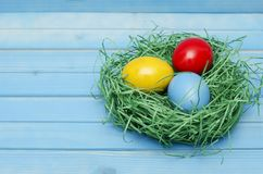 Easter card. Painted Easter eggs in a nest on a blue wooden background with copy space for congratulation Royalty Free Stock Photos