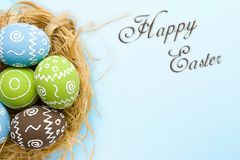Easter card. Painted Easter eggs in nest on pale blue background stock photos