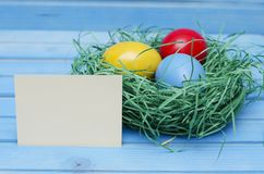 Easter card. Painted Easter eggs in a nest on a blue wooden background with copy space for congratulation Stock Images