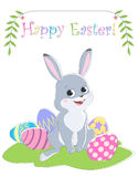Easter card with a picture of a rabbit sitting on the grass, painted eggs, greeting labels and branches with leaves. Stock Images