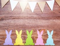 Easter card with rabbits and garland flags on wooden background royalty free stock photos