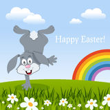 Easter Card with Rainbow and a Rabbit. A happy Easter card with a funny bunny rabbit in a meadow with green grass, flowers and the rainbow. Eps file available Stock Photo