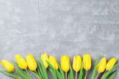 Easter card stone background with yellow tulips Stock Photography