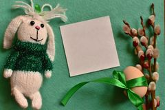 Easter card with toy bunny, catkins and egg on green background royalty free stock images