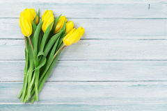 Easter card wooden background with yellow tulips Royalty Free Stock Photos