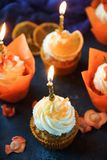 Easter carrot cupcakes with vanilla cream and caramel oranges. On dark stone background. Selective focus Royalty Free Stock Image