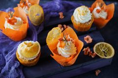 Easter carrot cupcakes with vanilla cream and caramel oranges. On dark stone background. Selective focus Royalty Free Stock Photo