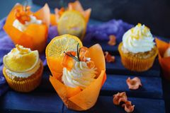Easter carrot cupcakes with vanilla cream and caramel oranges. On dark stone background. Selective focus Royalty Free Stock Photography