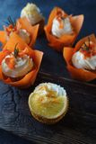 Easter carrot cupcakes with vanilla cream and caramel oranges. On dark stone background. Selective focus Stock Photo