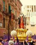 Easter Catholic Procession in Murcia, Spain. Penitent nazarenes carry a statue of the Virgin Mary near the Stock Photos