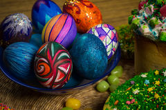 Easter celebrating cake, color eggs, straw backgrounds, food holidays photography. Blue plate with celebration multicolored painted easter eggs, yellow green Royalty Free Stock Image