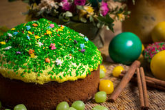 Easter celebrating cake, color eggs, straw backgrounds, food holidays photography. Easter celebrating family dinner, multicolored eggs, flowers, sweet sprinkled Stock Image