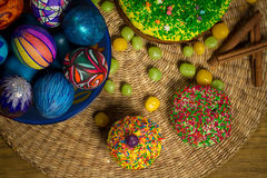 Easter celebrating cake, color eggs, straw backgrounds, food holidays photography. Easter celebrating family dinner, multicolored eggs, flowers, sweet sprinkled Royalty Free Stock Images