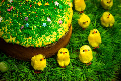 Easter celebrating cake on green grass with yellow toy chickens. Easter celebrating sweet cake decorated with sugar sprinkling on green fress grass with yellow stock photo