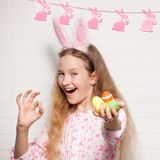 Child is holding a basket with Easter eggs Stock Photos