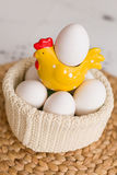 Easter celebration at home. A bright yellow hen with white organic eggs in a knitted pot. Straw tablecloth with eggs ready for Easter breakfast Stock Photography