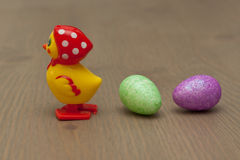 Easter Chick in Kerchief. Yellow chick in red polka dot kerchief with two pastel glitter Easter eggs on a wood surface Stock Images