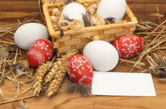 Easter chicken eggs in a basket  on a wooden background. Royalty Free Stock Photo