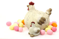 Easter chickens with some colorful eggs. Ceramic easter chickens surrounded by colorful easter eggs stock photos