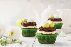 Easter chocolate cupcakes decorated with nest and candy eggs. For dessert. Festive pastry concept stock image