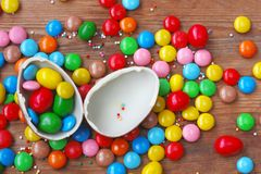 Easter chocolate egg, colorful candy on wooden table royalty free stock images